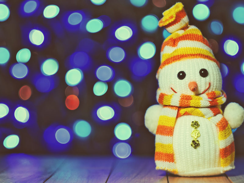 A hand-knit snowman with orange and yellow striped hat and scarf sits on a wooden table with blurry colored twinkle lights in the background