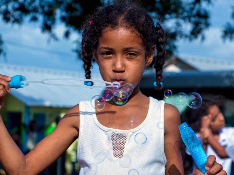 Little girl with pigtails looks at the camera while blowing bubbles