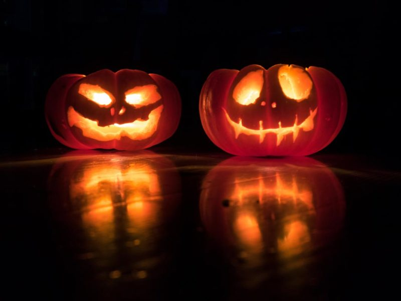 Two carved jack-o-lanterns, one with a silly face and one with a scary face, are lit from the inside and sit on a shiny table against a darkened background. Their faces are reflected in the table.