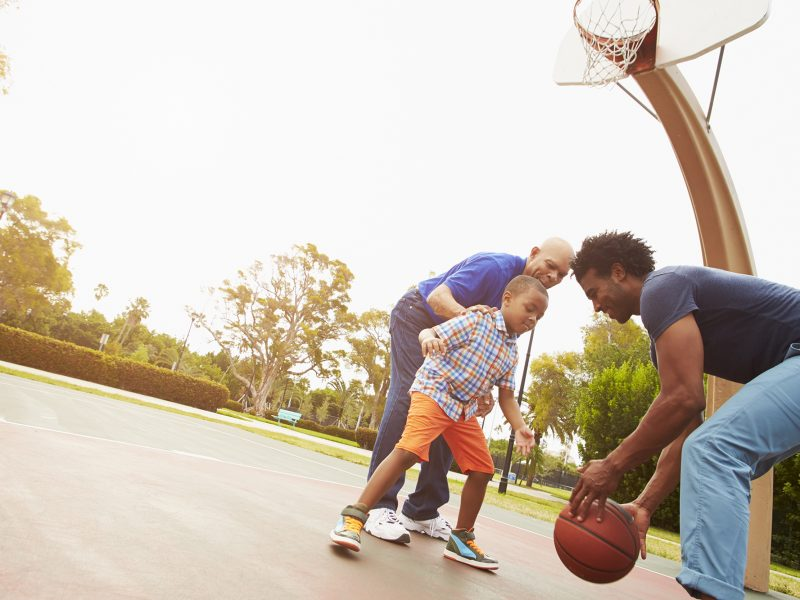 African Amercian Father with son and Grandfather playing basketball